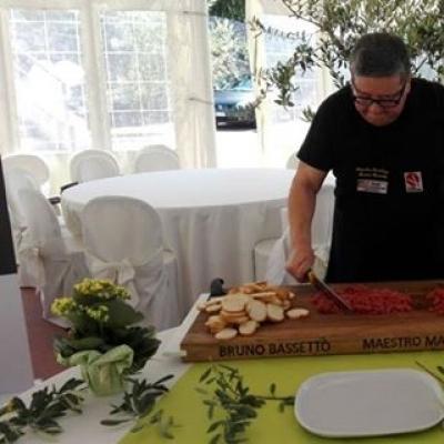 Il mastro macellaio Bruno Bassetto mentre prepara una battuta di carne di alta qualità con olio extra vergine Dop Garda