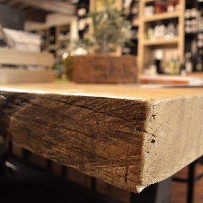 Una foto con una inquadratura che mette in risalto il pregiato legno del tavolo conviviale